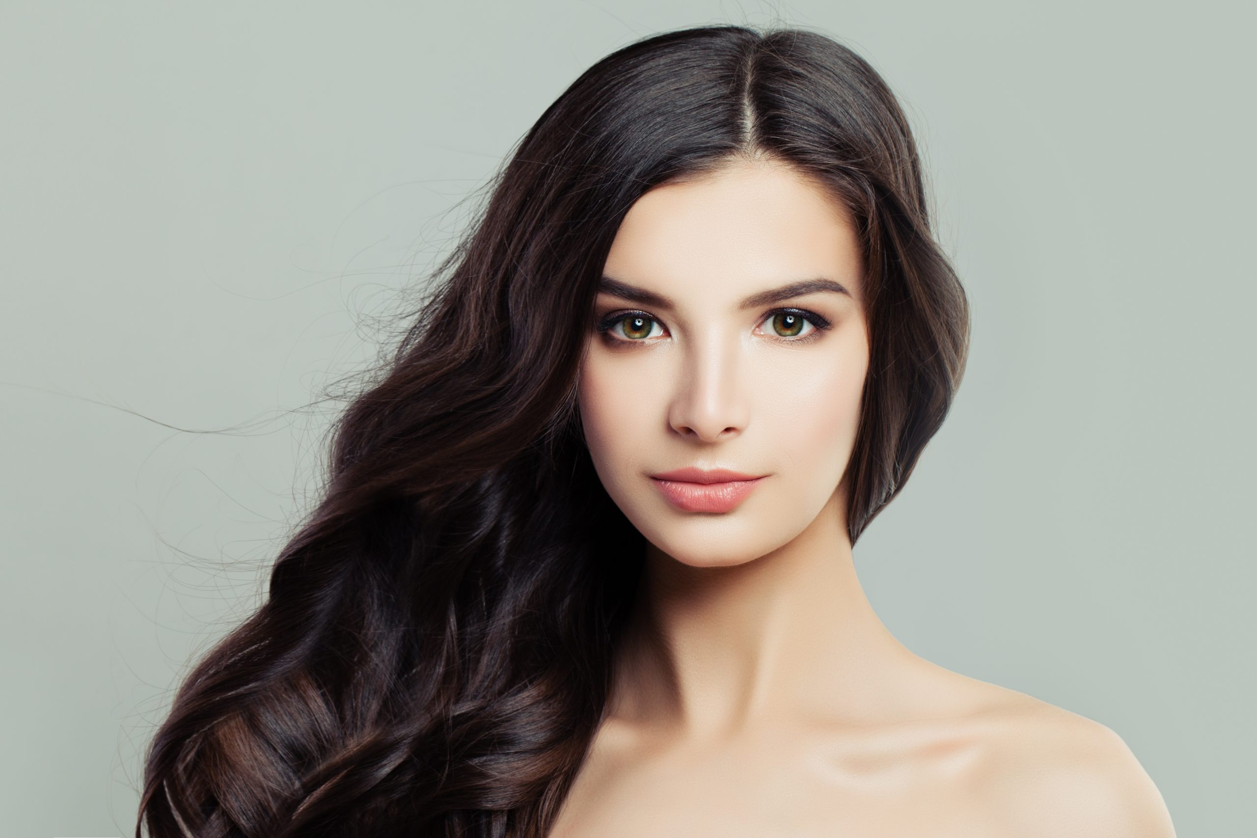 Beautiful young woman with long brown hairdo and clear skin. Facial treatment, cosmetology, beauty, hair care and spa