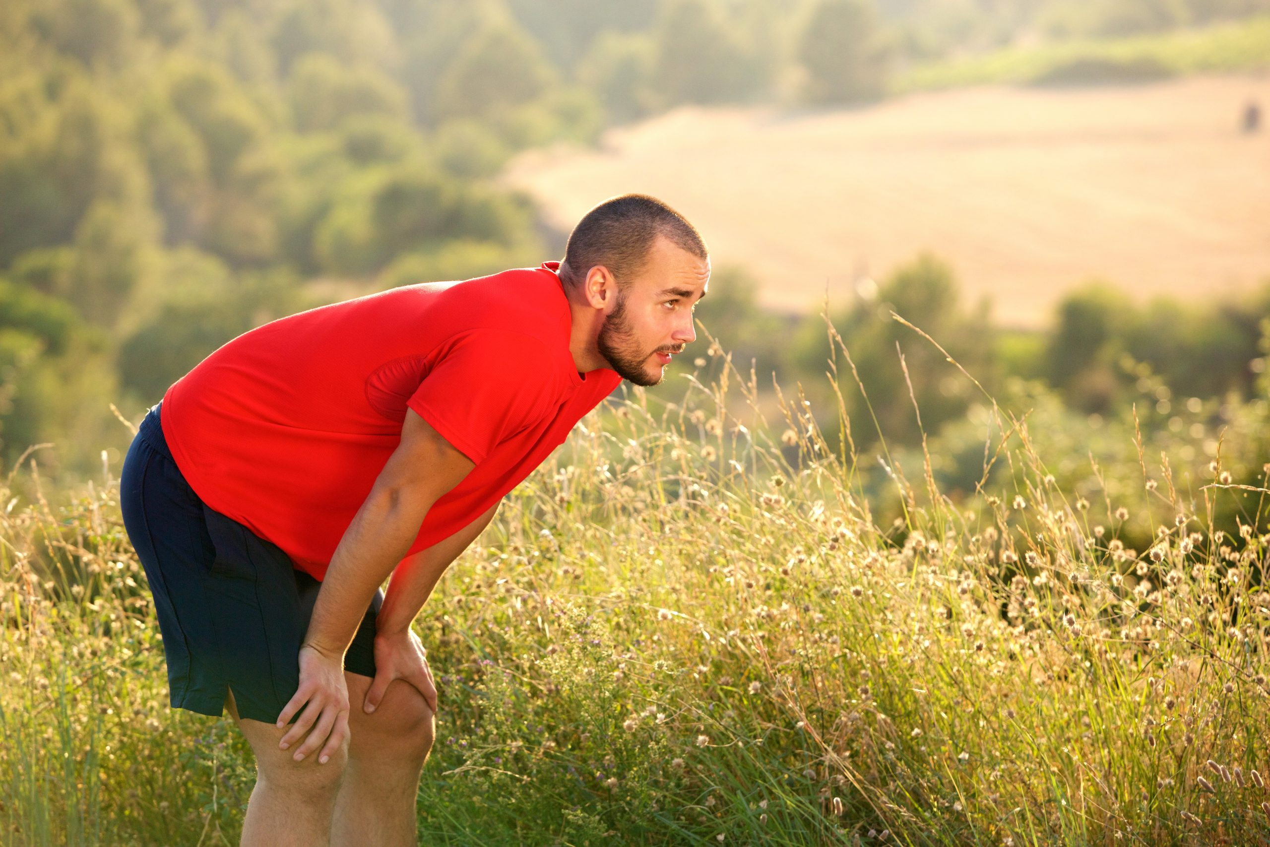 Tired sports man relaxing after running exercise workout